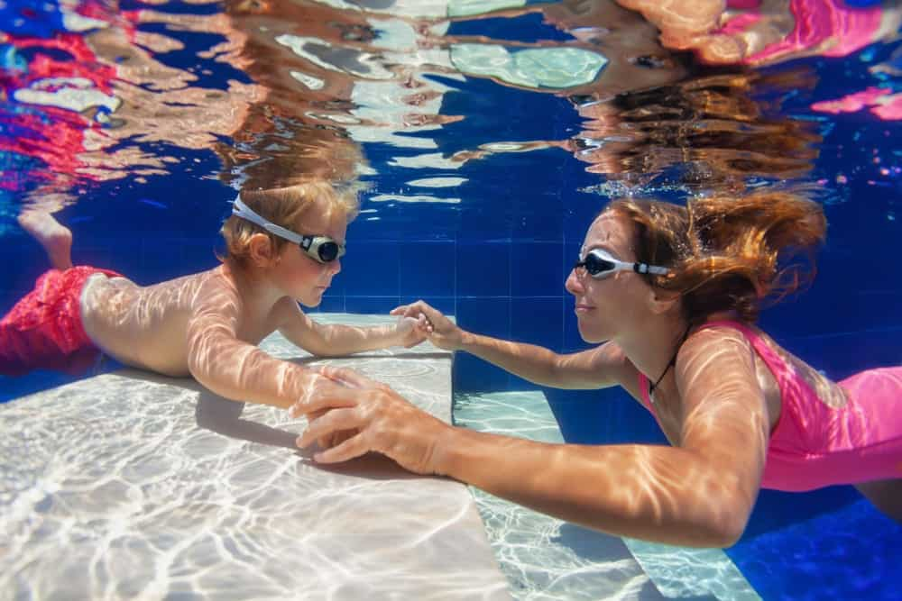 Mother helps child learn to swim in an indoor waterpark.