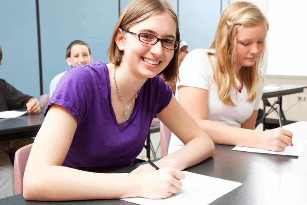 Happy student taking a test in school.