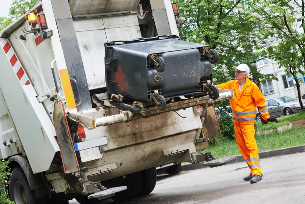 Garbage men picking up a residential dumpster along the street
