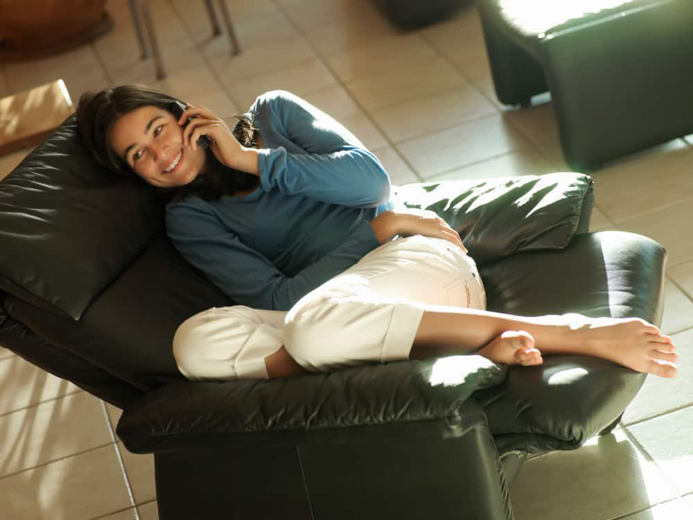 Girl talking on phone while sitting in a recliner